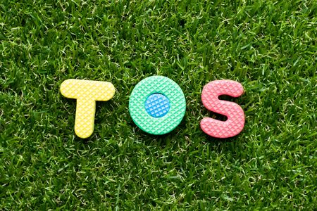 Toy foam letter in word TOS (abbreviation of Terms Of Service) on green grass background 스톡 콘텐츠