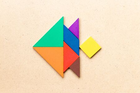 Color tangram puzzle in fish shape on wood background