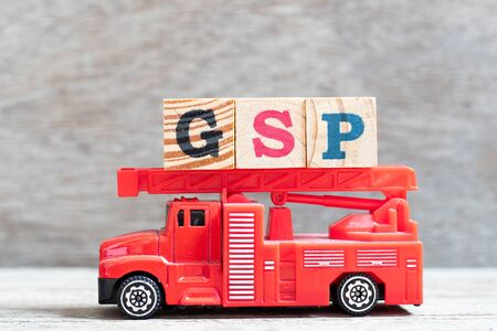 Red fire truck hold letter block in word GSP (Abbreviation of Good Storage Practice or Generalized System of Preferences or Gross State Product) on wood background
