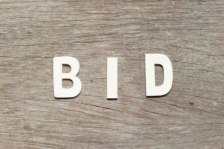 Alphabet letter in word bid on wood background