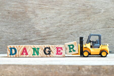 Toy forklift hold letter block R to complete word danger on wood background