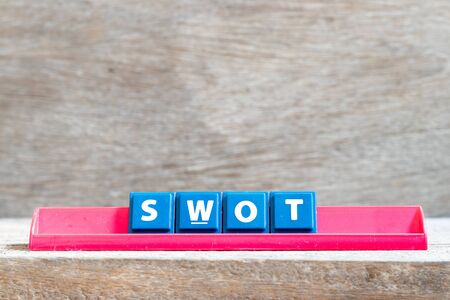 Tile letter on red rack in word swot (abbreviation of strength, weakness, opportunities, threats) on wood background