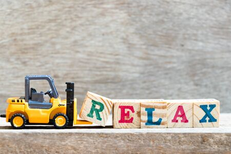 Toy forklift hold letter block r to complete word relax on wood background