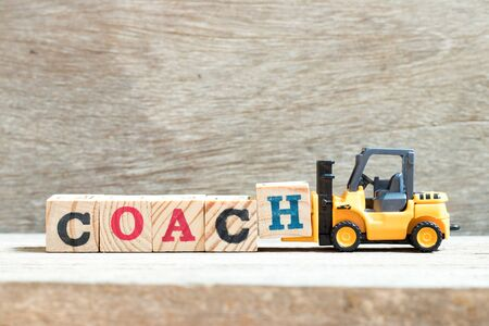 Toy forklift hold letter block h in word coach on wood background