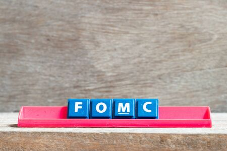 Tile letter on red rack in word fomc (abbreviation of federal open market committee) on wood background Zdjęcie Seryjne