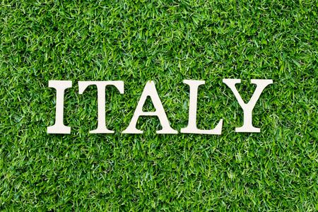 Wood alphabet letter in word italy on green grass background