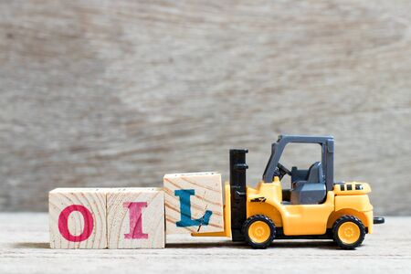 Toy forklift hold letter block l to complete word oil on wood background