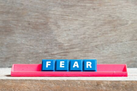 Tile letter on red rack in word fear on wood background