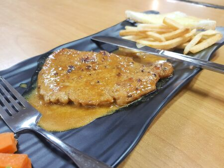 Grilled pork steak with frech fries on dish background