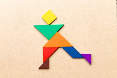 Color tangram puzzle in running man shape on wood background Archivio Fotografico - 128703498