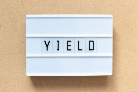 White lightbox with word yield on wood background Imagens - 128820423