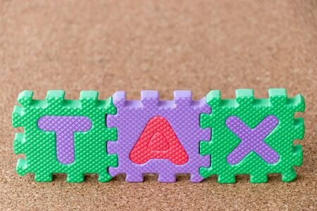 Colorful toy foam alphabet in word tax on cork board background Imagens - 128827157