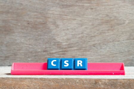 Tile letter on red rack in word CSR (Abbreviation of corporate social responsibility) on wood background