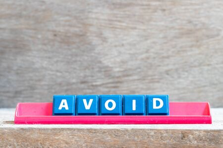 Tile letter on red rack in word avoid on wood background