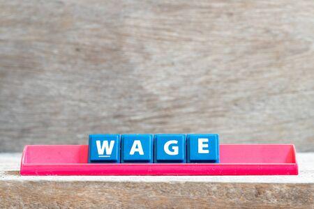 Tile letter on red rack in word wage on wood background Reklamní fotografie