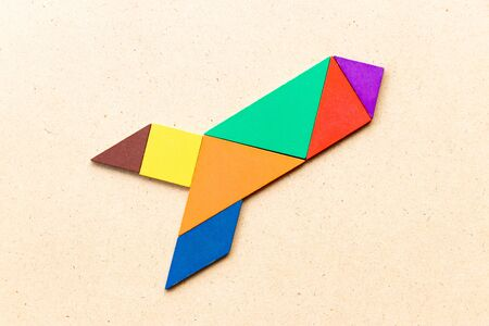 Color tangram puzzle in rocket or missile shape on wood background (Concept for new experience, start up project)
