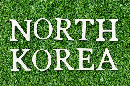 Wood alphabet letter in word north korea on green grass background
