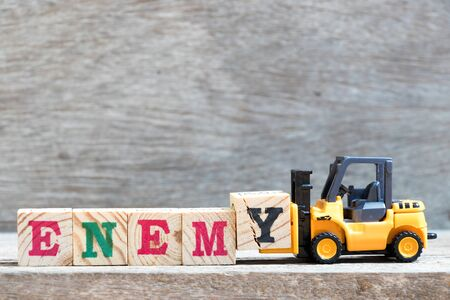 Toy forklift hold letter block y to complete word enemy on wood background Stockfoto