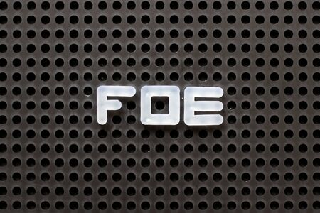 Black color pegboard with white letter in word foe