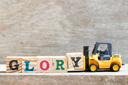 Toy forklift hold letter block y to complete word glory on wood background