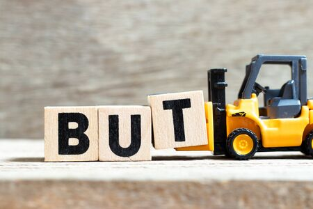 Toy forklift hold letter block t to complete word but on wood background