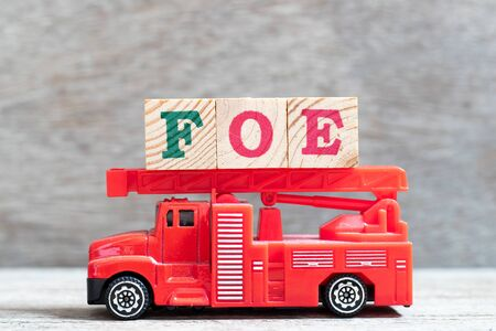 Red fire truck hold letter block in word foe on wood background