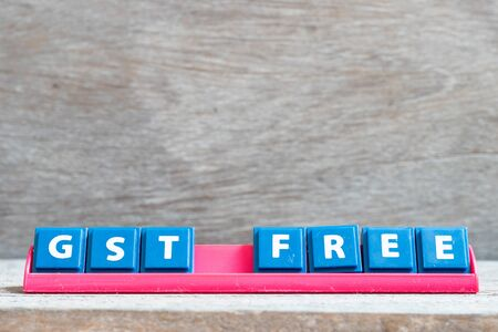 Tile letter on red rack in word GST (Abbreviation of Goods and Services Tax) on wood background