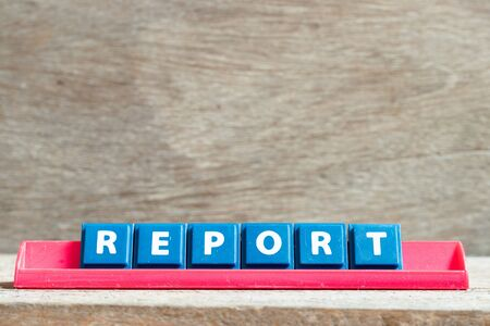 Tile letter on red rack in word report on wood background