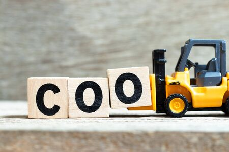 Toy forklift hold letter block O to complete word COO (abbreviation Chief operating officer) on wood background Stock Photo