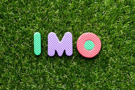 Toy foam letter in word  IMO (Abbreviation of in my opinion) on green grass background 写真素材