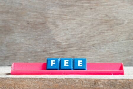 Tile letter on red rack in word fee on wood background