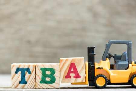 Toy forklift hold letter block  in word TBA (abbreviation of to be announced) on wood background