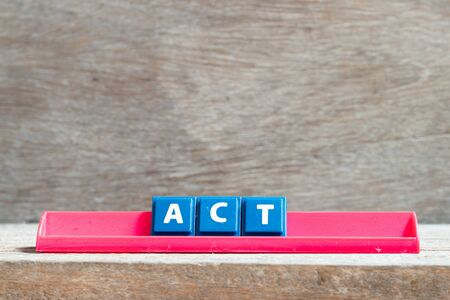 Tile letter on red rack in word act on wood background