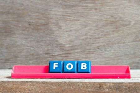 Tile letter on red rack in word FOB (abbreviation of Free On Board) on wood background