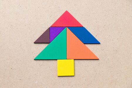 Color tangram in Pine or christmas tree shape on wood background Stock fotó