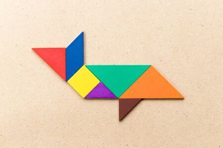 Color tangram puzzle in shark or whale shape on wood background