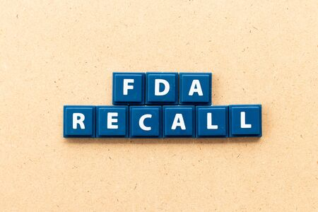 Tile letter in word fda recall on wood background