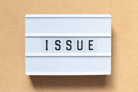 White light box with word issue on wood background