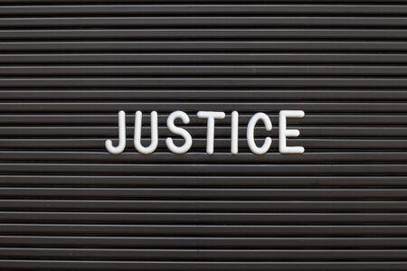 Black color felt letter board with white alphabet in word justice background