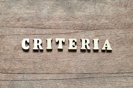 Letter block in word criteria on wood background