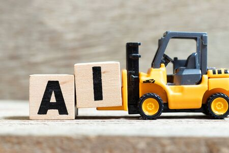 Toy forklift hold letter block i to complete word AI on wood background