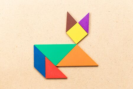 Color tangram puzzle in lying down cat shape on wood background