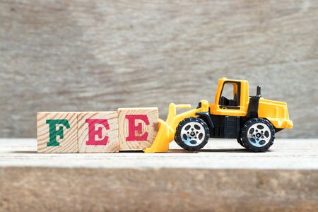 Toy bulldozer hold letter block e to complete word fee on wood background Stockfoto