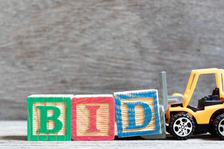 Spielzeuggabelstapler halten Buchstabenblock d, um das Wortgebot auf Holzhintergrund zu vervollständigen