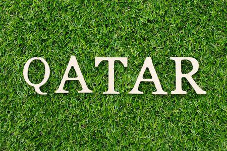 Wood alphabet letter in word Qatar on green grass background 版權商用圖片