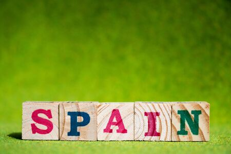 Letter block in word spain on artificial green background