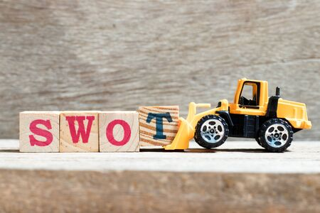 Toy bulldozer hold letter block T to complete word swot (abbreviation of strength, weakness, opportunities, threats) on wood background Stok Fotoğraf