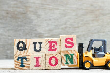 Toy forklift hold letter block s, n to complete word question on wood background Stock fotó