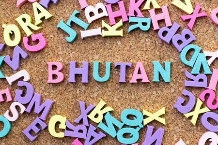 Color alphabet in word Bhutan with another letter as frame on cork board background