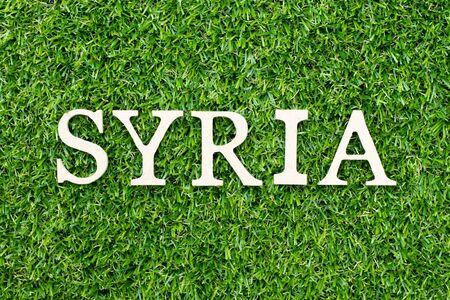 Wood alphabet letter in word Syria on green grass background